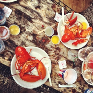 Lobster meal on paper plates in rustic setting